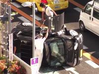 名古屋で路駐していた車に衝突して横転した軽自動車から女性ドライバーを助け出す人たち。