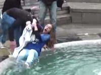 これは大損害・・・。噴水に落とされた女性⇒を撮影しようとしたカメラマンが・・・。