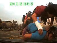 二人乗りのスクーターが突っ込んできて後部座席の女性がぶっ飛んでいく。