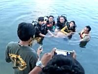 川から引き上げた水死体を前に記念撮影をするダイビングチームの映像が話題に。