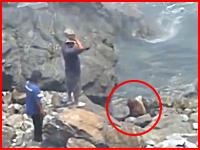 日頃の恨み!とばかりに漁師らしき二人組が大きな石をアシカの頭に落として殺そうとしている様子