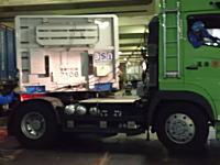 職人技。フェリーの貨物スペースにコンテナ台車を押し込むトレーラー運転手のワザ。