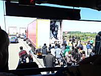 これはカオス。何処からともなく現れた男たちが渋滞中のトラックの扉を開けて不法入国を試みている様子。