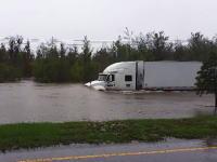 川かと思った。洪水でかなり水位のある中を豪快に突き進む大型トレーラーの映像。