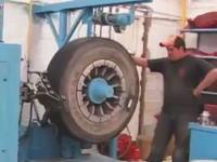 再生タイヤの作り方。古くなった大型タイヤにトレッドを貼りつける作業の様子。