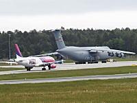 手前の旅客機と比べて分かるこのデカさ。米軍最大の輸送機の大迫力な離陸風景。