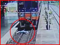 体が切断されるように線路に横たわる。監視カメラが捉えた電車飛び込み自殺の瞬間。
