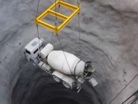 ダムの建設現場。クレーンで釣った生コン車ごと深い深い穴の中へ。