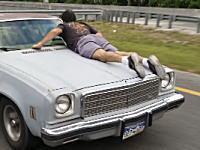 笑い事じゃねえ。結構なスピードで走るボンネットにしがみついている男が撮影される。