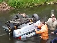川に落ちて逆さまになってしまった車から二人の乗員を助け出す観客たち