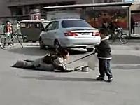 路上で下半身まひの母親を引っ張るようにして歩く子供の物乞い。中国。