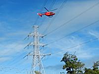 お仕事動画。ヘリコプターに吊られて送電線のメンテナンスをする作業員さん