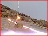 岩場で遊ぶ人たちのすぐ近くに落雷した稲妻が岩の表面を伝わる凄い映像。