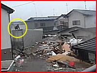 津波の新しい動画。濁流の中で必死に電線に掴まって助かった人と建物の上に乗って流される人