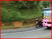 カーブでバスをインから抜こうとしたバイクが対向車と正面衝突する決定的瞬間