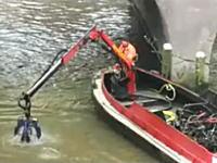 自転車UFOキャッチャー 橋の下に投げ入れられた自転車を撤去する作業員
