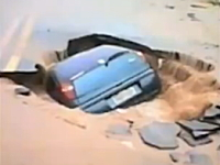 洪水で陥没して空いた道路の穴に車がゆっくりとのみこまれていく様子。