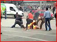 広場で自分自身に火を付けて自殺を図った男性とそれを消し止めようとする人たち