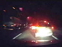 深夜の高速道路で追い越し車線に車を停止させて口論している二台の車。